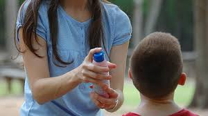 woman applying insect repellent to a child