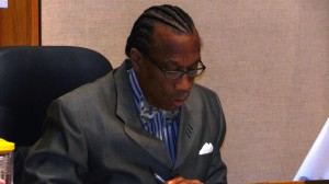 Commissioner John Wiley Price reads a resolution in appreciation of Leonard Willis' service to the county and the community. Willis was not in attendance while the resolution was read.