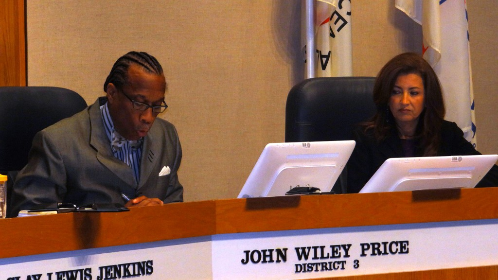 Commissioner John Wiley Price reads a resolution honoring former City Councilman Leo Chaney as Commissioner Elba Garcia, right, listens.